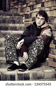 Sad young hippie man sitting on the steps