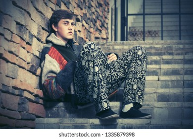 Sad young hipster man sitting on the steps