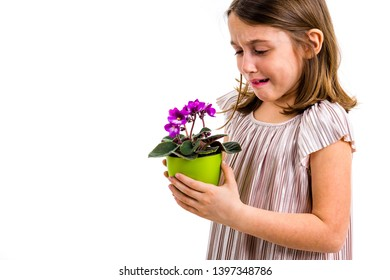 Sad young little girl holding flower pot mourning family loss. Child grieving over losing loved ones. Girl looking at flower pot, sad face, crying. Profile view, studio shot, isolated on white back.