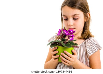 Sad young little girl holding flower pot mourning family loss. Child grieving over losing loved ones. Girl is looking at the flower pot, with sad face, crying. Profile view, studio shot, isolated