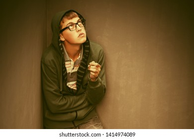 Sad young man in depression smoking cigarette at the wall Stylish trendy male model in green hoodie
