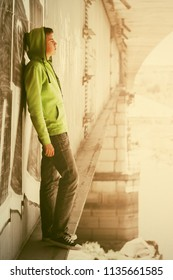 Sad young man in depression standing on the bridge Teenage male model wearing light green hoodie and dark grey jeans