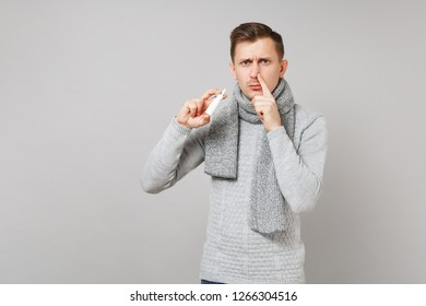 Sad young man in gray sweater, scarf holding nasal drops covering nostril with finger isolated on grey background. Healthy lifestyle ill sick disease treatment cold season concept. Mock up copy space