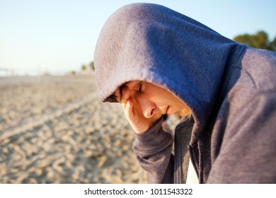 Sad Young Man in a Hoodie on the Beach