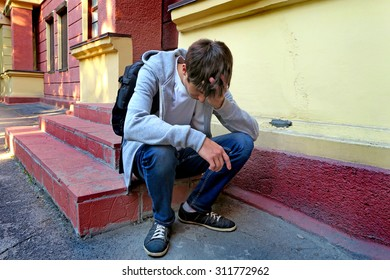Sad Young Man with Knapsack on the Porch of the House