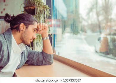 Sad young man looking down upset, hand on forehead. Closeup portrait of a handsome guy wearing formal white shirt, gray blouse sitting near window at a table in living room. Mixed race, indian turkish