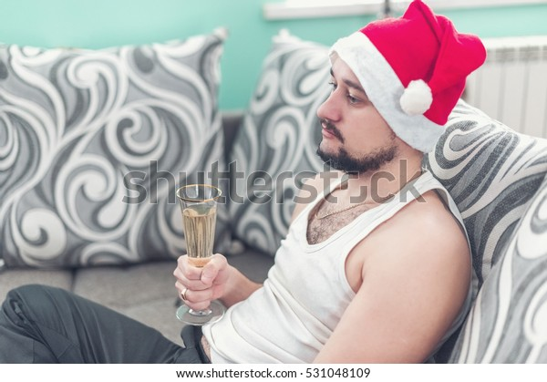 Sad young man lying on the sofa at Christmas. A lazy guy in a Christmas hat drinking champagne. Holiday procrastination concept