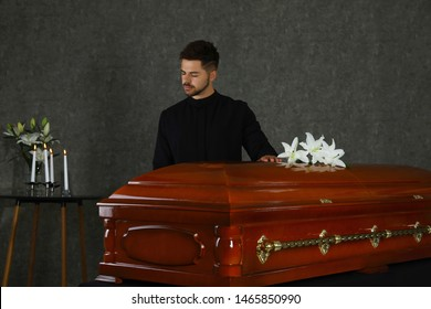 Sad young man near casket with white lilies in funeral home