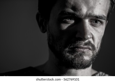 sad young man on a dark background, sad emotions, black and white photography, close-up