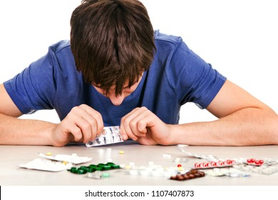 Sad Young Man with a Pills on the Table