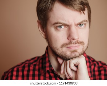 Sad young man, portrait on the beige background.