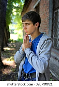 Sad Young Man praying on the Brick Building Background