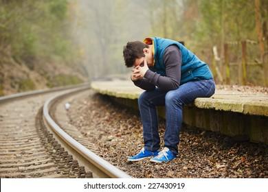 Sad young man at the railway station