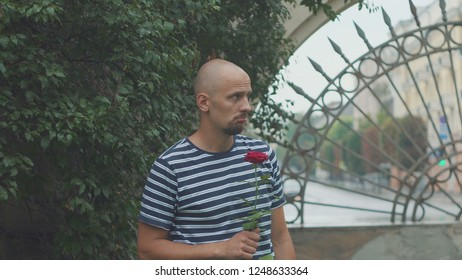 sad young man with a rose waiting for a late woman