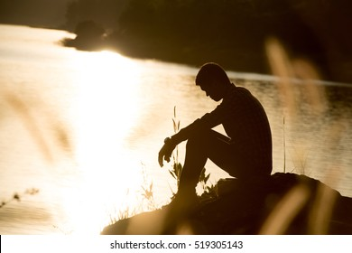Sad young man silhouette worried on the meadow at sunset ,Silhouette concept