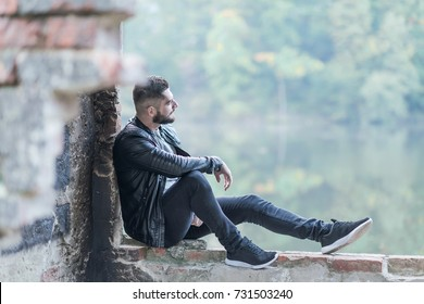 Sad young man sits at the lake and thinks.Relaxed and looking somewhere in the distance