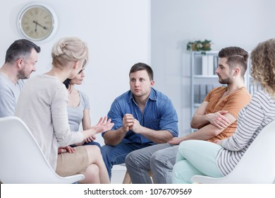 Sad, young man sitting in a bright office during a group meeting for gambling addicts