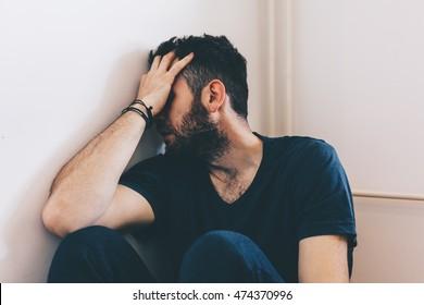 Jovem triste sentado no canto da sala