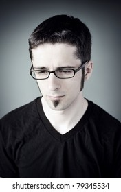 A sad young man wearing glasses.