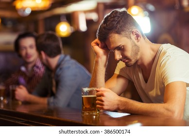 Sad young man in white t-shirt is looking at glass of beer while sitting at bar counter in pub, in the background two other men