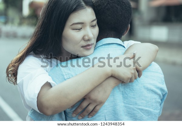 Sad young multiethnic couple or friends hugging outdoors. Multiracial lovers having date. Reconciliation or love concept