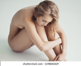Sad young naked woman sits over the grey background. Gorgeous  woman with nude body. Nice portrait of a blonda girl with long curly hair.