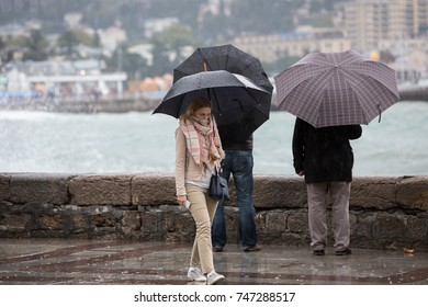 Sad young pretty blonde woman walking with black umbrella along embankment on rainy day, people with umbrellas on background/