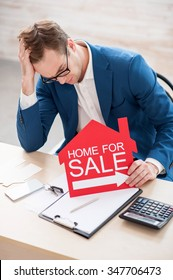 Sad young realtor is sitting at the desk and looking down with frustration. He is holding a placard in the shape of house