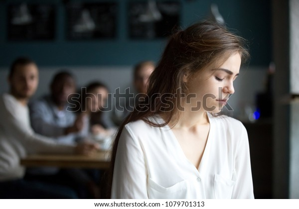Sad young woman avoiding ignoring bad friends suffering from gossiping, bullying, unfair attitude or discrimination, frustrated millennial girl feeling upset, hurt and offended sitting alone in cafe