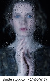 Sad young woman behind the window glass with raindrops. Female in retro vintage dress looking through the glass on black background. Focus on water drops.