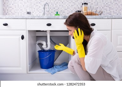 Sad Young Woman Calling Plumber In Front Of Water Leaking From Sink Pipe
