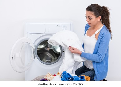Sad young woman with clothes near washing machine at home.