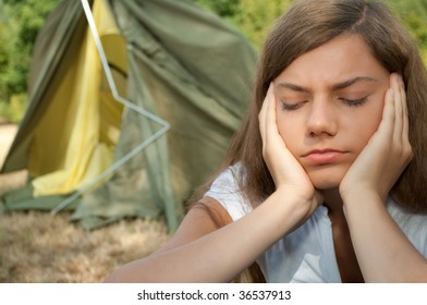 Sad young woman with collapsing tent in background.