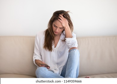 Sad young woman desperately looking at smartphone screen, waiting call from boyfriend or lover