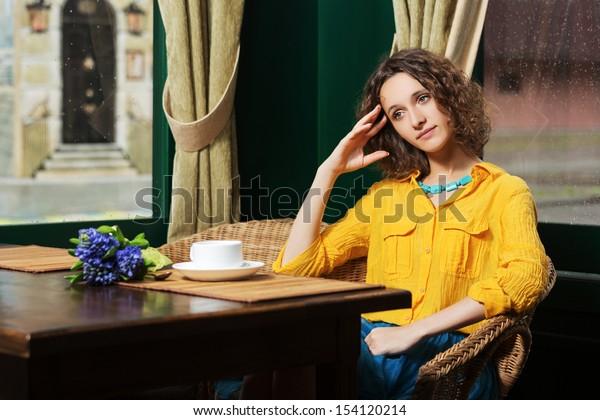 Sad young woman drinking tea at restaurant
