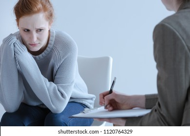 Sad young woman with eating disorders during meeting with psychotherapist