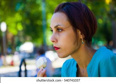 sad young woman eating ice cream, thoughtful girl eating ice cream.