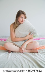 sad young woman embrancing her pillow