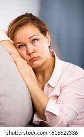 Sad young woman with fair hair alone longs sitting on sofa at home