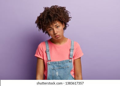 Sad young woman has Afro hairstyle, apathy in eyes, tilts head, isnt eager to do something after hard work, feels overworked, wears casual t shirt, denim overalls, looks unhappy straight at camera