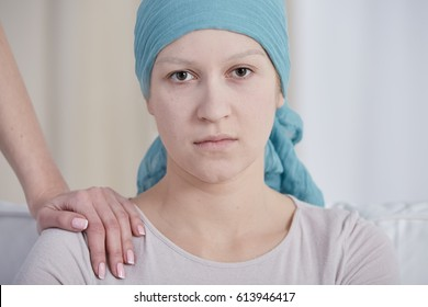 Sad young woman with her friend's hand on her shoulder and wearing blue headscarf