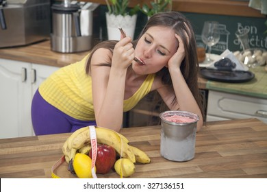 Sad young woman leaning on the kitchen counter at home and eating ice cream. She is too depressed to keep a diet.