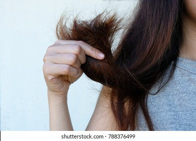 Sad Young Woman With Long Hair In Hand ,Hair Damage, Health And Beauty Concept.