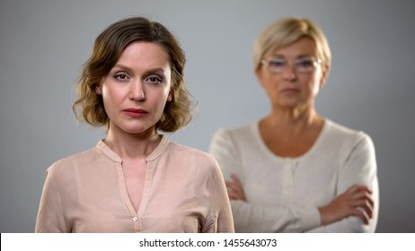 Sad young woman looking in camera, strict senior mother standing behind, problem