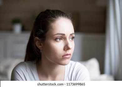 Sad young woman looking in distance thinking about relationships problems, upset hurt girl view from window sorrow about breakup with boyfriend, disappointed female feeling blue having troubles