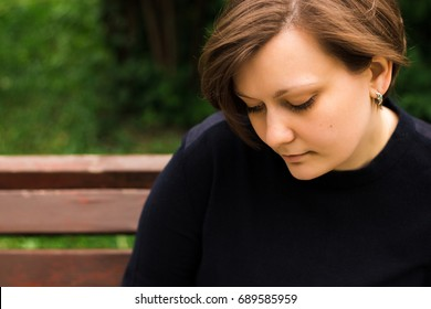 Sad young woman looking down portrait