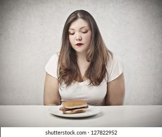 sad young woman looking hot dog