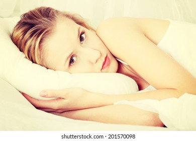 Sad young woman lying in bed