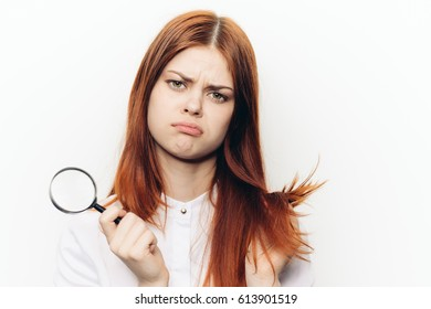 Sad young woman with magnifier in hand, light background