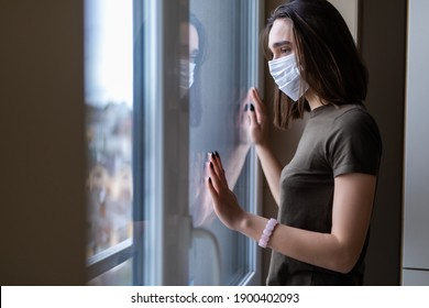 Sad young woman in a medical mask looks out of the window. Quarantine during the coronavirus pandemic.